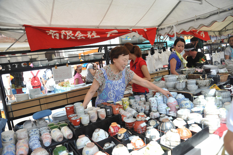A pottery dealer presents her wide selection dishes to potential buyers during the Seto Pottery Autumn Festival held in Seto