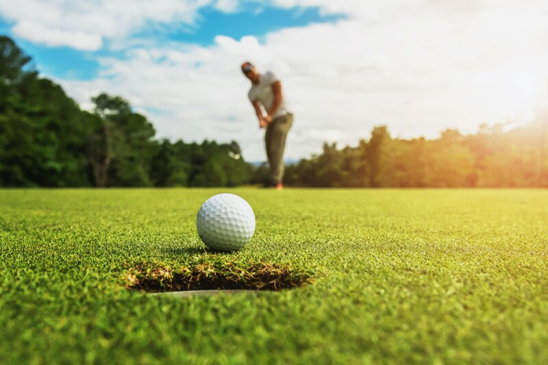 A golf ball just ahead of a hole with a golfer in the far distance. Strategies to hit a better short approach shot in golf.