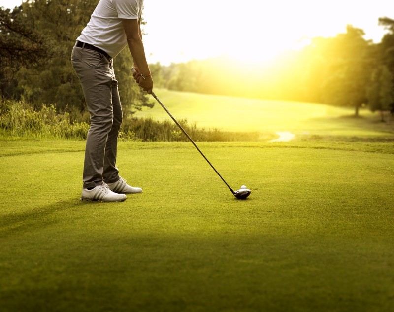 Man Golfing with sunshine and course in front of him