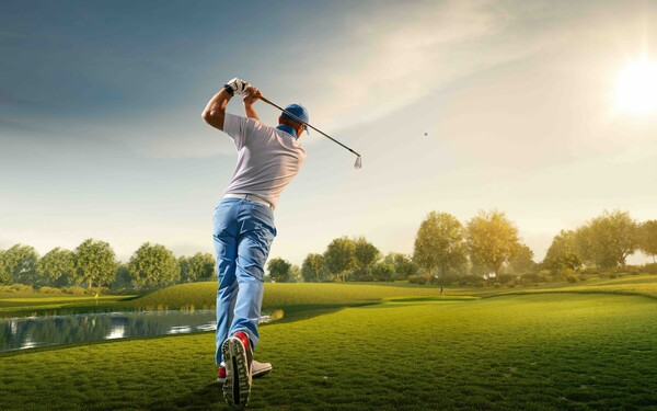 A male golfer swinging a club on a golf course. 4 Strategies to Hit Better Approach Shots in Golf